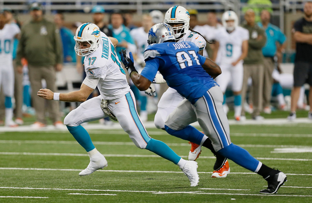 . Miami Dolphins quarterback Ryan Tannehill (17) is chased by Detroit Lions defensive end Jason Jones (91) during the first half of an NFL football game in Detroit, Sunday, Nov. 9, 2014. (AP Photo/Paul Sancya)