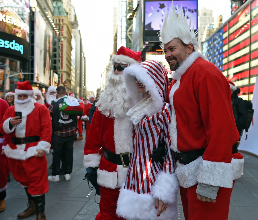 . People dressed as Santa Claus and Mrs. Claus pose for photos in Times Square as hundreds of Santas gather for the annual Santacon festivities on December 13, 2014 in New York. AFP PHOTO/DON EMMERT/AFP/Getty Images