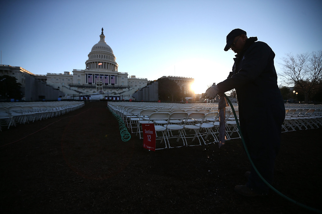 . A worker prepares to wipe down chairs, set up in front of the U.S. Capitol Building on January 20, 2013 in Washington, DC. Washington is preparing for the second inauguration of U.S. President Barack Obama, which will take place on January 21.  (Photo by Mark Wilson/Getty Images)