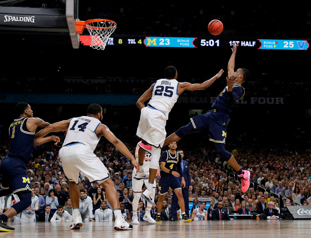. Michigan\'s Muhammad-Ali Abdur-Rahkman (12) shoots over Villanova\'s Mikal Bridges (25) during the first half in the championship game of the Final Four NCAA college basketball tournament, Monday, April 2, 2018, in San Antonio. (AP Photo/David J. Phillip)