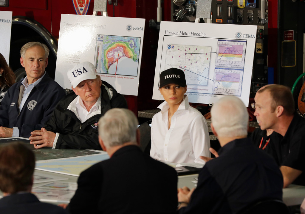 . President Donald Trump, flanked by Texas Gov. Greg Abbott and first lady Melania Trump listens during a briefing on Harvey relief efforts, Tuesday, August 29, 2017, at Firehouse 5 in Corpus Christi, Texas. (AP Photo/Evan Vucci)