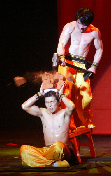 The Peking Acrobats perform at Laxson Auditorium Wednesday night. - Here the Peking Acrobats smash 4 bricks with a sledge hammer over another one's head. - halley photo 1/18/06