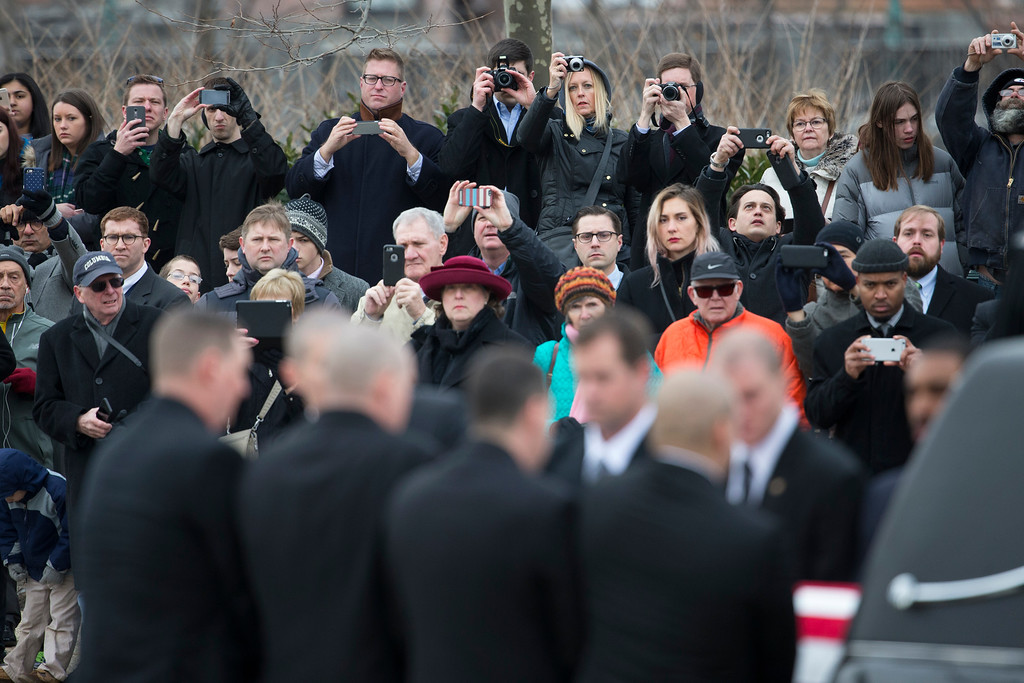 . People watch as the casket of Supreme Court Justice Antonin Scalia arrives at the Supreme Court in Washington, Friday, Feb. 19, 2016. Thousands of mourners will pay their respects Friday for Justice Antonin Scalia as his casket rests in the Great Hall of the Supreme Court, where he spent nearly three decades as one of its most influential members. (AP Photo/Evan Vucci)