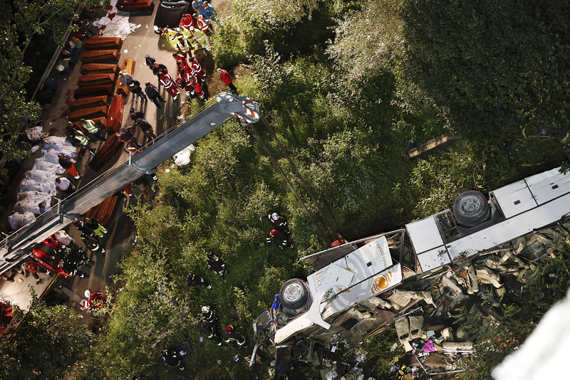 . Rescuers prepare the coffins of victims of a bus crash on July 28, 2013 on the road between Monteforte Irpino and Baiano, southern Italy. At least 36 people were killed and several more injured after a coach carrying pilgrims plunged off a motorway flyover in southern Italy, rescue services said.    AFP PHOTO / STINGER / AGENZIA CONTROLUCESTRINGER/AFP/Getty Images