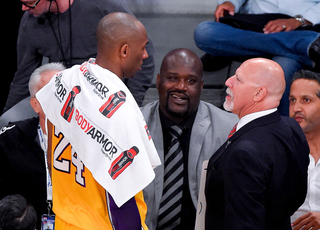 . Former player Shaquille O\'Neal, middle, watches as Los Angeles Lakers forward Kobe Bryant and trainer Gary Vitti talk during the first half of Bryant\'s last NBA basketball game, against the Utah Jazz, Wednesday, April 13, 2016, in Los Angeles. (AP Photo/Mark J. Terrill)