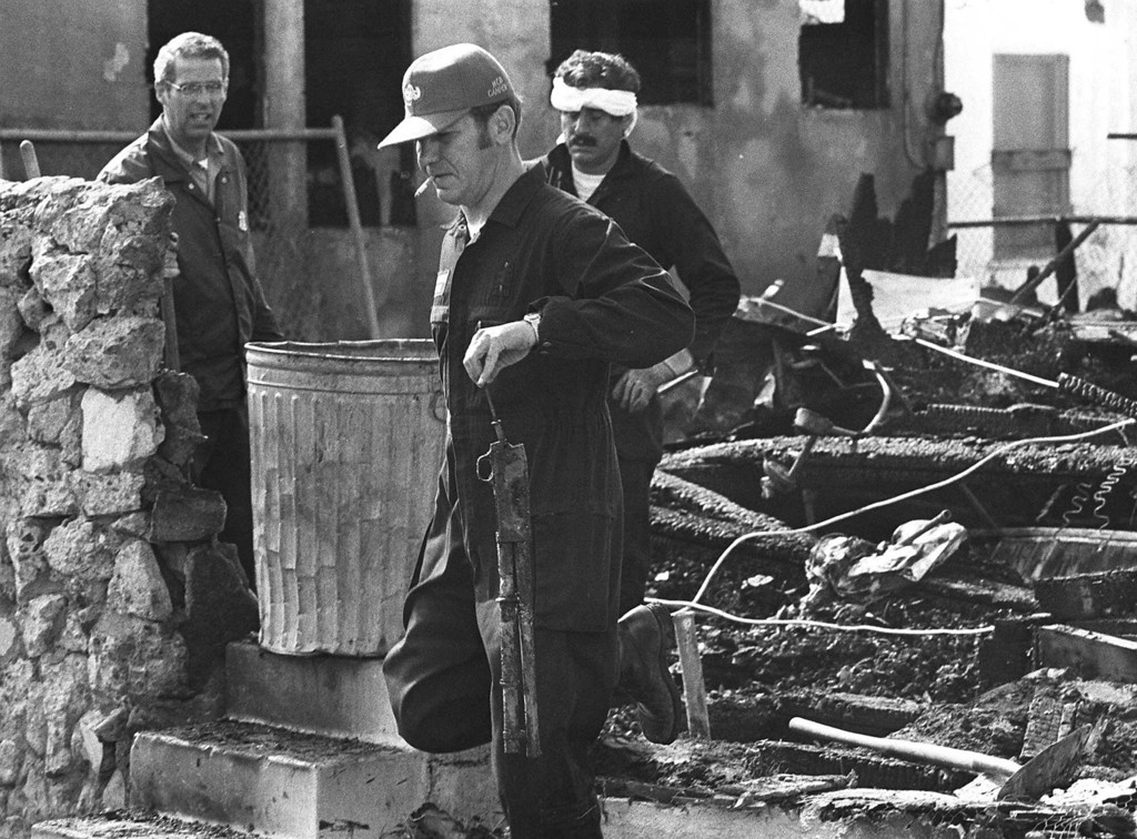 . A Los Angeles police officer carries a shotgun from the burned wreckage of a house during Saturday\'s investigation May 18, 1974 of the shootout Friday in which five persons were killed.  The people that died in this house were believed to be members of the Symbionese Liberation Army.  Policemen in background are carrying a can of debris from the scene to be searched for clues.  (AP Photo)