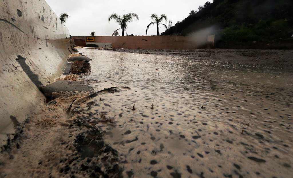 . Raindrops splash in water, mud and debris in a basin slowly filling up in Duarte, Calif., in a threatened area below a burn area know as the Fish Fire, as a powerful storm moves into Southern California Friday, Feb. 17, 2017. The saturated state faces a new round of wet weather that could trigger flooding and debris flows. (AP Photo/Reed Saxon)