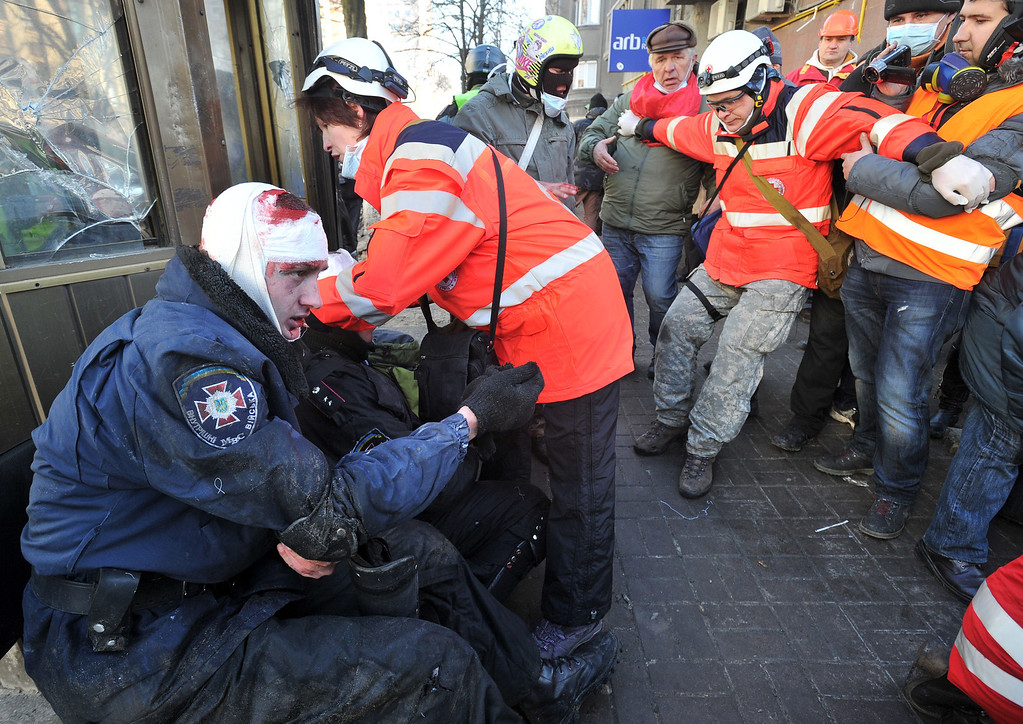 . Red Cross workers give first aid to policemen wounded during clashes with anti-government protester in Kiev on February 18, 2014. AFP PHOTO/GENYA SAVILOV/AFP/Getty Images