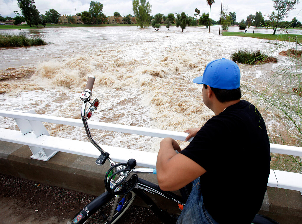 . A man watches floodwaters surge under an overpass Monday, Sept. 8, 2014, in Scottsdale, Ariz. The remnants of Hurricane Norbert pushed into the desert Southwest and swamped Arizona Monday, breaking the previous record for rainfall in a single day in Phoenix. (AP Photo/Rick Scuteri)
