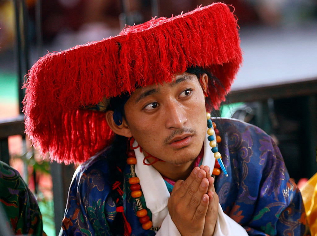 ". A traditional Tibetan artist listens to spiritual leader the Dalai Lama during an event organized to celebrate the 78th birthday of the Dalai Lama at a Tibetan Buddhist monastery in Bylakuppe, about 220 kilometers (137 miles) southwest of Bangalore, India, Saturday, July 6, 2013. Speaking after an interfaith meeting, he said 150,000 Tibetans living abroad represent ""6 million Tibetans (in China) who have no freedom or opportunity to express what they feel.\"" (AP Photo/Aijaz Rahi)"