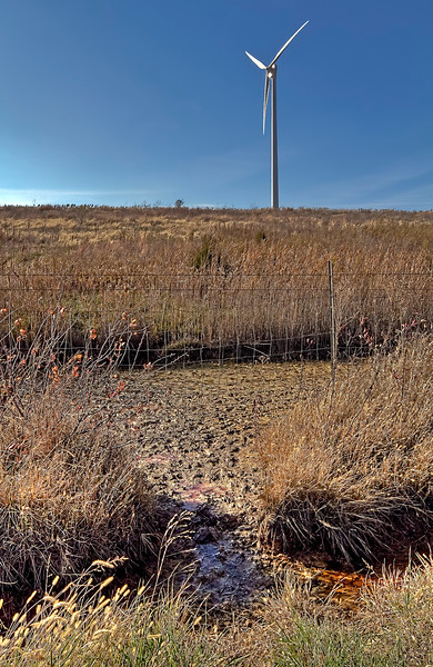 """This wind turbine was erected on the site of an old 60 ft high coal slurry pond. It was dedicated in 2009 by Gov. Quinn with the words """"... a site that once produced coal has been turned into a one-of-a-kind green initiative."""" Whoops, that stuff leaching out from the bottom doesn't look too green to me!"""