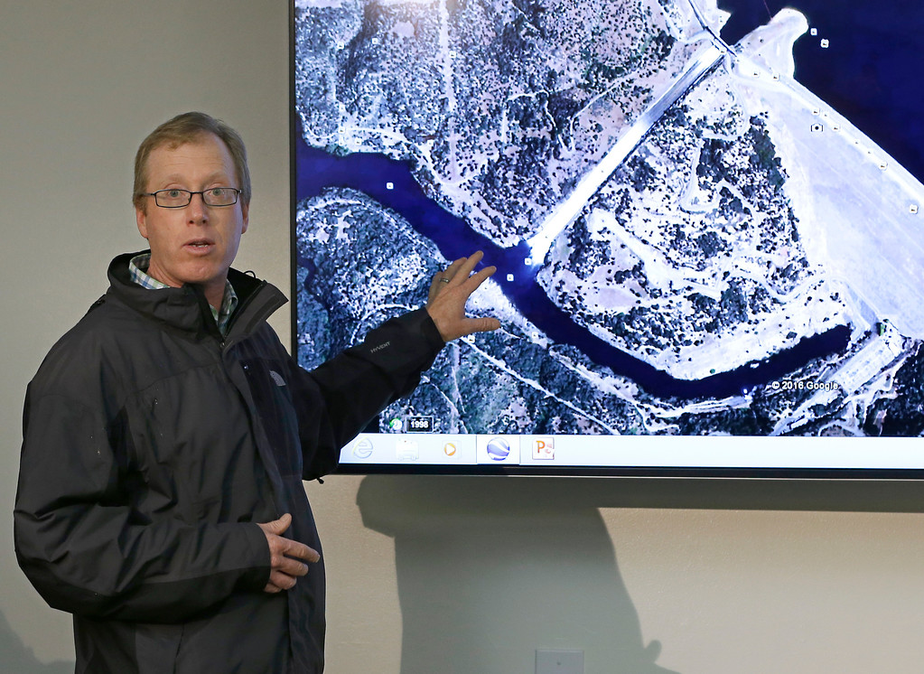 . Eric See, of the California Department of Water Resources, gestures to an aerial photo of the Oroville Dam spillway during a news conference, Thursday, Feb. 9, 2017, in Oroville, Calif. Earlier this week, chunks of concrete went flying off the spillway, creating a 200-foot-long, 30-foot deep hole. (AP Photo/Rich Pedroncelli)
