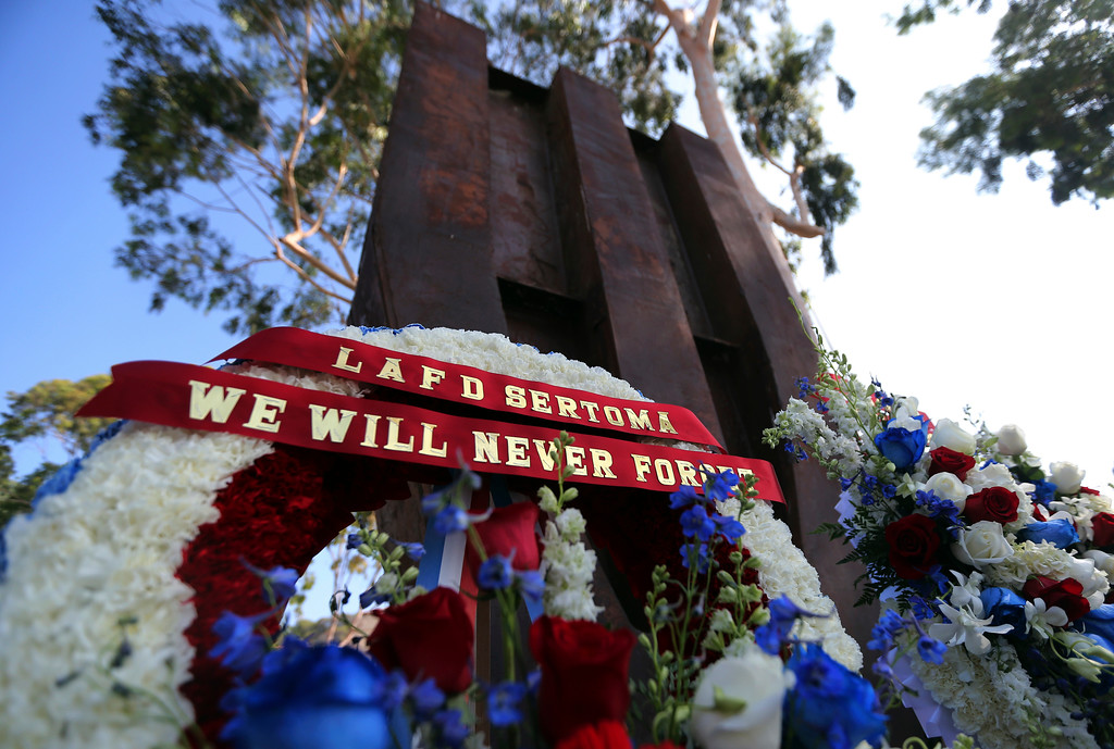 ". A wreath with the words ""We Will Never Forget\"" is seen during a ceremony marking the 17th anniversary of the Sept. 11, 2001 terrorist attacks on the Untied States, at the Los Angeles Fire Department\'s training center Tuesday, Sept. 11, 2018. In the background is the largest fragment of the World Trade Center outside New York.  (AP Photo/Reed Saxon)"