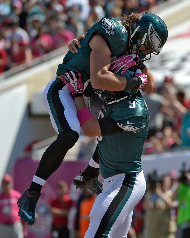 . Philadelphia Eagles quarterback Nick Foles (9) celebrates with wide receiver Riley Cooper (14) after Foles scored on a four-yard touchdown run against the Tampa Bay Buccaneers during the first quarter of an NFL football game Sunday, Oct. 13, 2013, in Tampa, Fla. (AP Photo/Phelan M. Ebenhack)