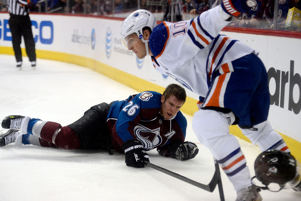 . Paul Stastny (26) of the Colorado Avalanche gets knocked to the ice by Shawn Horcoff (10) of the Edmonton Oilers during the first period March 12, 2013 at Pepsi Center. Horcoff was called for hooking on the play. (Photo By John Leyba/The Denver Post)
