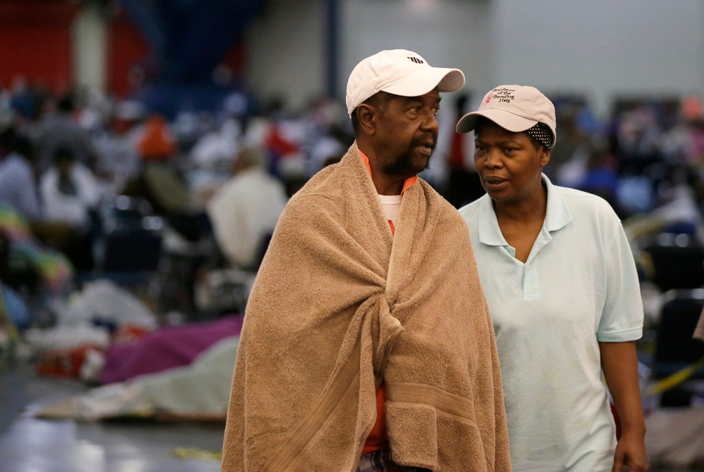 . Ezekiel Lyons, left, walks with his wife at the George R. Brown Convention Center that has been set up as a shelter for evacuees escaping the floodwaters from Tropical Storm Harvey in Houston, Texas, Tuesday, Aug. 29, 2017. (AP Photo/LM Otero)