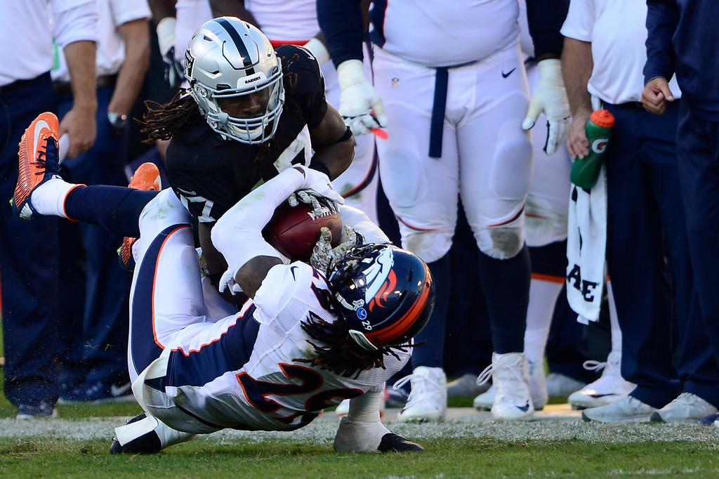. OAKLAND, CA. November 09, - Wide receiver Denarius Moore #17 of the Oakland Raiders makes a catch over cornerback Bradley Roby #29 of the Denver Broncos at O.co Coliseum November 09, 2014 Oakland, CA (Photo By Joe Amon/The Denver Post)