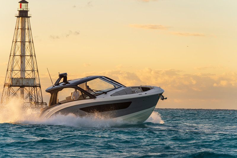 2021-Sundancer-370-Outboard-DAO370-lifestyle-starboard-bow-three-quarter-couple-lighthouse-00741.jpg