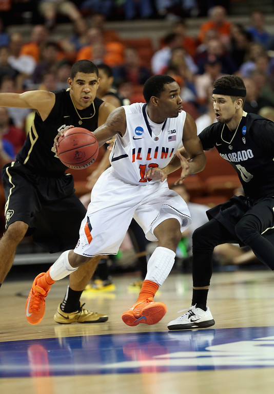 . AUSTIN, TX - MARCH 22:  Tracy Abrams #13 of the Illinois Fighting Illini dribbles past Askia Booker #0 of the Colorado Buffaloes during the second round of the 2013 NCAA Men\'s Basketball Tournament at The Frank Erwin Center on March 22, 2013 in Austin, Texas.  (Photo by Stephen Dunn/Getty Images)
