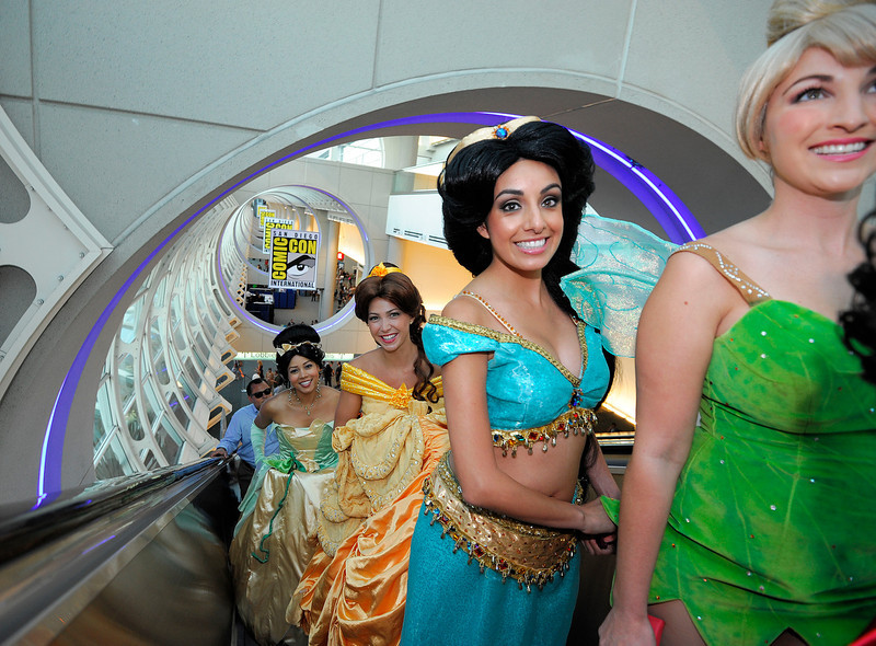 . Fans dressed as Disney princesses ride the escalator as they get their credentials during the Preview Night event on Day 1 of the 2013 Comic-Con International Convention on Wednesday, July 17, 2013 in San Diego, Calif. (Photo by Denis Poroy/Invision/AP)