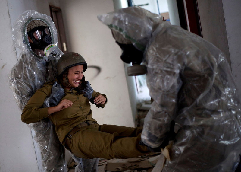 . Israeli soldiers of the Home Front Command rescue unit wear protective gear during a drill in Azur, near Tel Aviv, Israel, Tuesday, May 28, 2013. Israel has launched a national civil defense drill, which the army said this year will focus on the threat of unconventional weapons at a time of growing regional tensions. (AP Photo/Ariel Schalit)