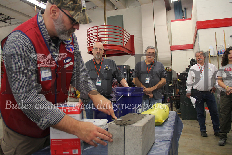 Attendants of Saturday's Flood Disaster Workshop in Butler watch as a Lowe's employee demonstrates hydraulic cement. Photo by Eric Jankiewicz