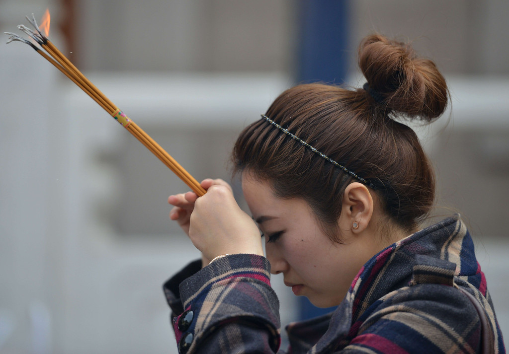 """. A Chinese woman prays at Jing An Temple to mark the start of the Year of the Horse in Shanghai on January 31, 2014. Millions of families gathered together to usher in the Year of the Horse, kicking off a week of celebrations in the country\'s most important holiday by visiting temples, indulging in feasts of dumplings and rice cakes and exchanging hongbao, red envelopes stuffed with \""""lucky money\"""".   AFP PHOTO/Peter PARKS/AFP/Getty Images"""
