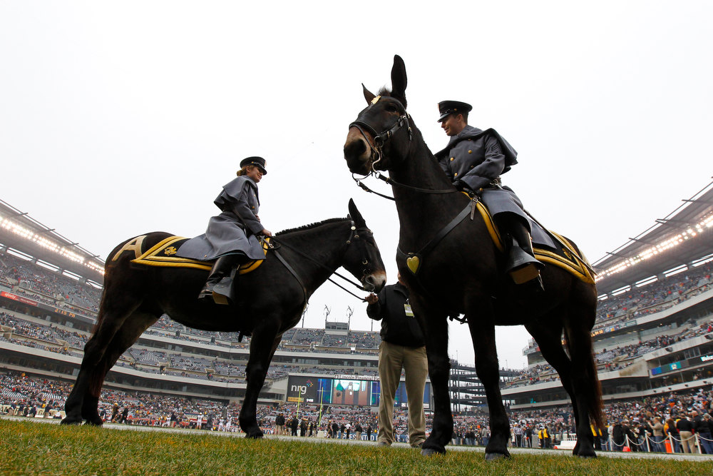 . Army Cadets Katherine Deaton, left, atop Ranger 3 and Nels Estvold atop Stryker wait for the start an NCAA college football game against Navy, Saturday, Dec. 8, 2012, in Philadelphia. (AP Photo/Matt Rourke)
