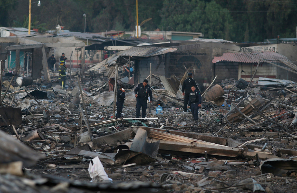 . Local policemen walk through the scorched ground of the open-air San Pablito fireworks market, in Tultepec, outskirts of Mexico City, Mexico, Tuesday, Dec. 20, 2016.  An explosion ripped through Mexico�s best-known fireworks market on the northern outskirts of the capital Tuesday, injuring scores and killing dozens, according to Mexican Federal Police. (AP Photo/Eduardo Verdugo)