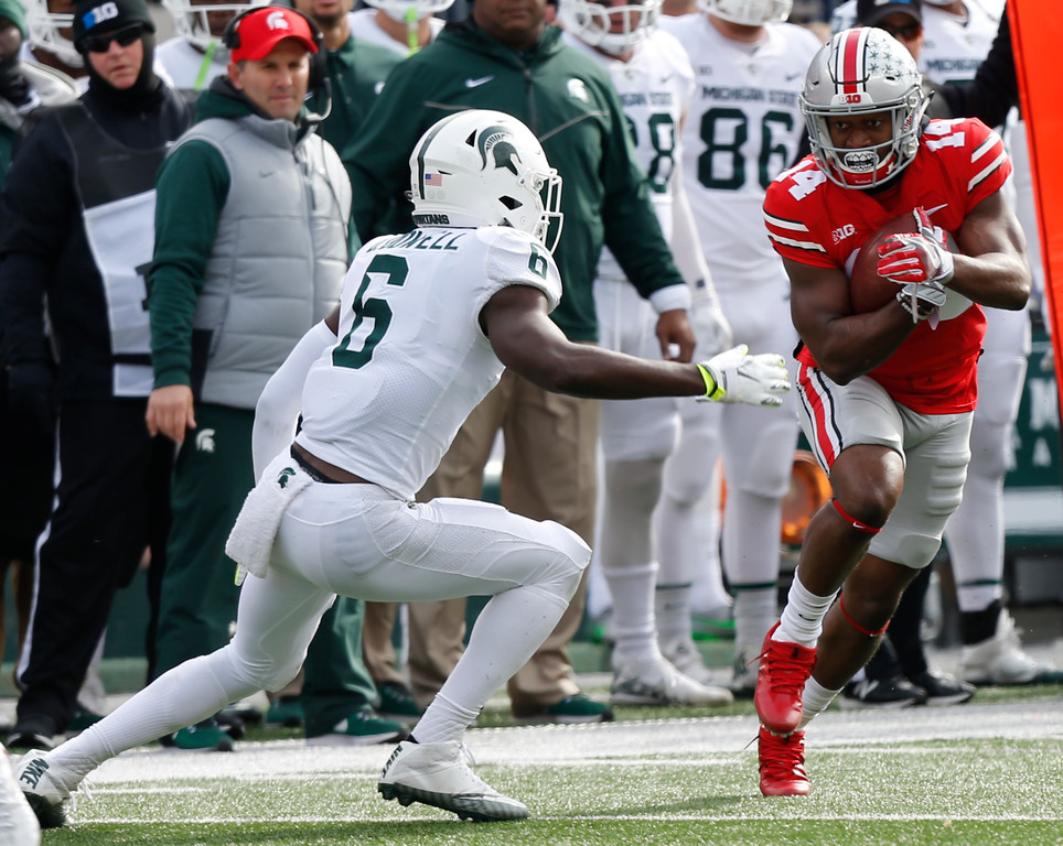 . Ohio State receiver K.J. Hill, right, runs after a catch as Michigan State safety David Dowell defends during the first half of an NCAA college football game Saturday, Nov. 11, 2017, in Columbus, Ohio. Ohio State beat Michigan State 48-3. (AP Photo/Jay LaPrete)
