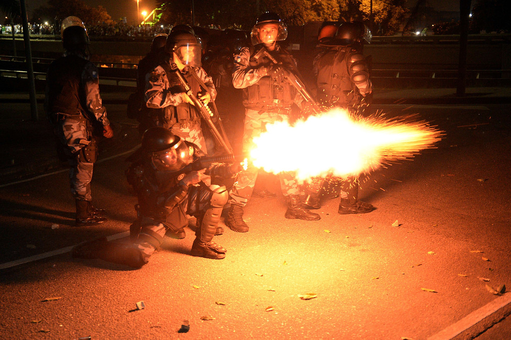 . Anti riot police officers fire gaz cans during a protest part of what is now called the \'Tropical Spring\' against corruption and price hikes, on June 20, 2013, in Rio de Janeiro.     AFP PHOTO / LLUIS  GENE/AFP/Getty Images