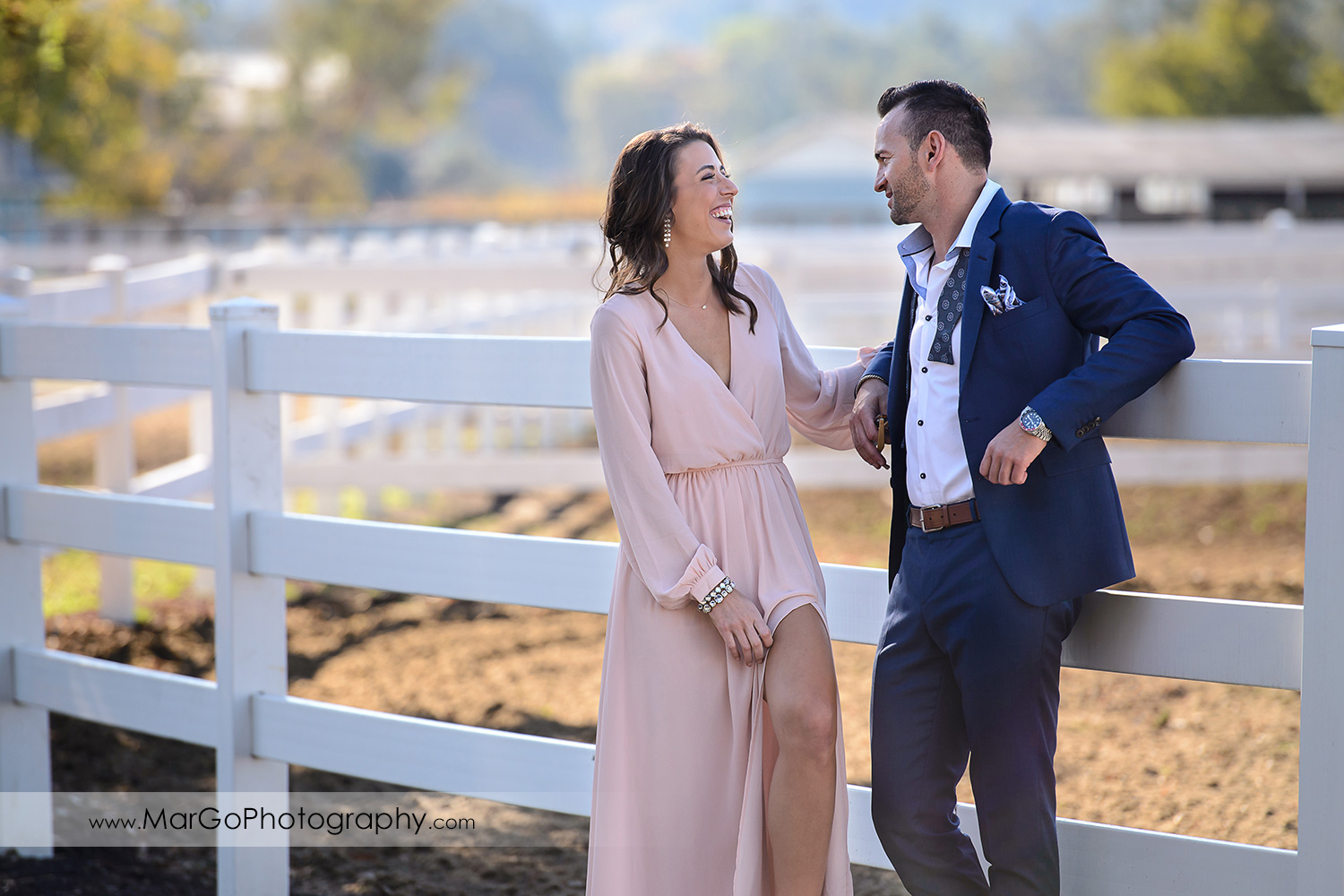 woman in pink dress and man in blue suit standing next to each other and laughing during Napa Valley engagement session at Tamber Bey Vineyards in Calistoga