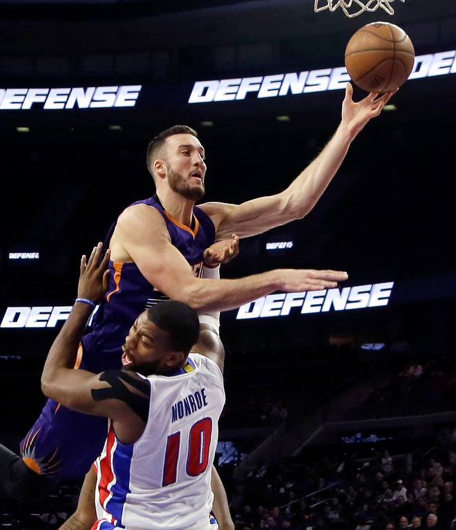. Detroit Pistons forward Greg Monroe (10) is fouled by Phoenix Suns center Miles Plumlee (22) during the second half of an NBA basketball game in Auburn Hills, Mich., Wednesday, Nov. 19, 2014. (AP Photo/Carlos Osorio)