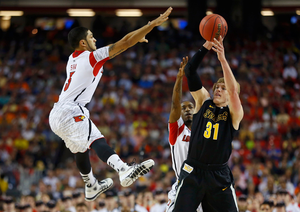 . Wichita State Shockers guard Ron Baker (R) is guarded by Louisville Cardinals\' Peyton Siva (L) and Russ Smith (rear) in the first half of their NCAA men\'s Final Four basketball game in Atlanta, Georgia April 6, 2013. REUTERS/Jeff Haynes