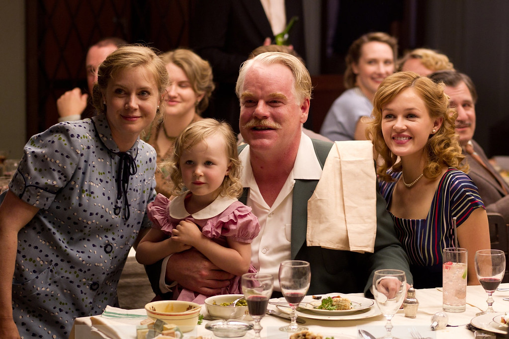 """. Lancaster Dodd (Philip Seymour Hoffman) with his family and followers in Paul Thomas Anderson\'s American epic set in 1950 \""""The Master.\"""" Courtesy the Weinstein Company."""