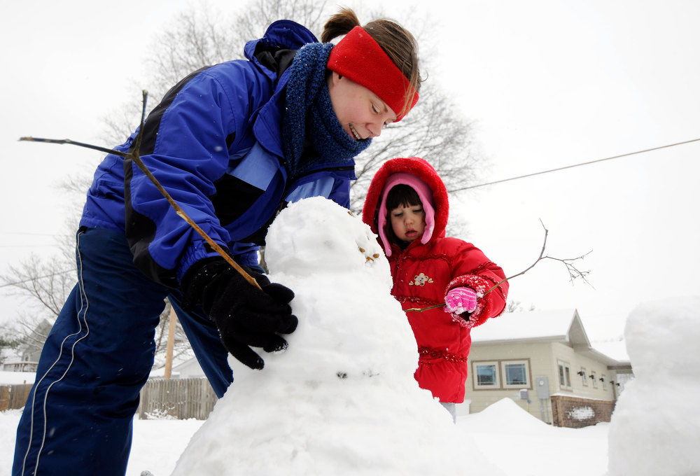. Laura Morthland and her daughter Lily Morthland, 2, fit their small snowman with arms that were collected from a bush outside their home in Murphysboro, Ill. Wednesday, Dec. 26, 2012 in Murphysboro. (AP Photo/The Southern Illinoisan, Aaron Eisenhauer)