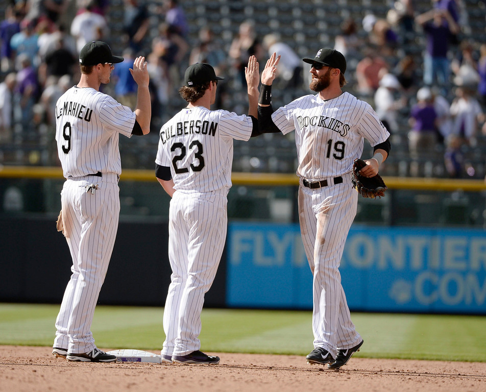 . Colorado Rockies players, left too right, DJ LaMahieu, Charlie Culberson and Charlie Blackmon come off the field in celebration after defeating the Chicago White Sox 10-4 at Coors Field Wednesday afternoon, April 09, 2014. (Photo By Andy Cross / The Denver Post)