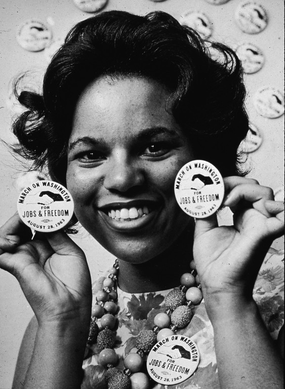 . A female demonstrator smiles as she holds protest buttons next to her face at the March on Washington, Washington, DC, August 28, 1963. (Photo by Hulton Archive/Getty Images)