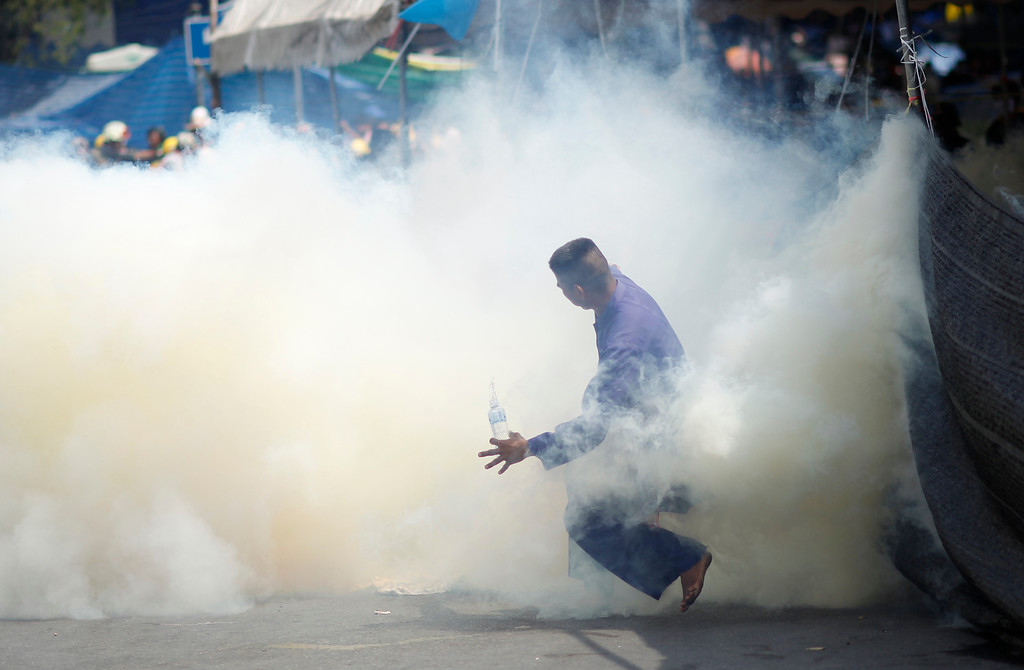 . An anti-government protester is caught in tear gas during clashes with riot police in Bangkok, Thailand, Tuesday, Feb. 18, 2014. Clashes between police and anti-government demonstrators in Bangkok left three people dead and 57 others injured Tuesday as riot police attempted to clear out protest camps around the Thai capital. (AP Photo/Wally Santana)