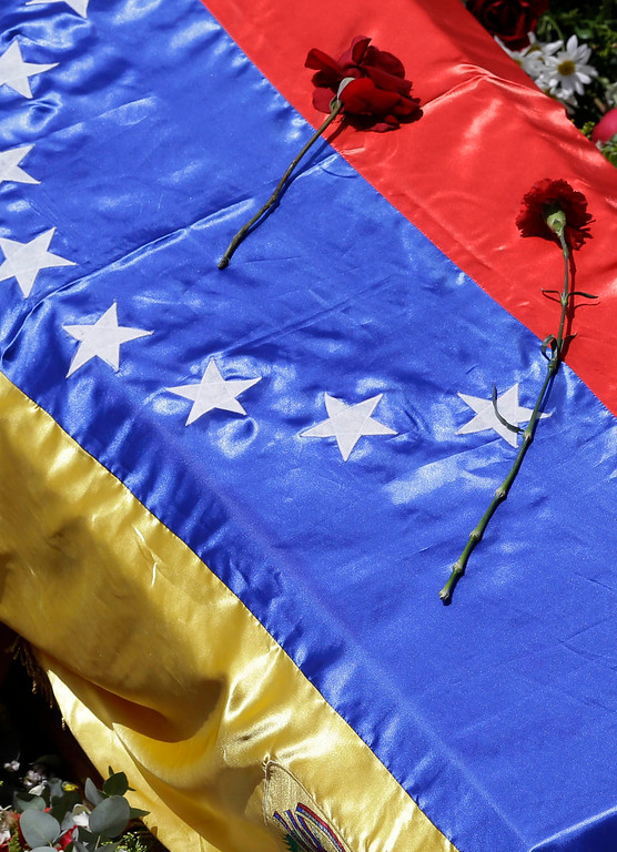 . Flowers lay on the flag-draped coffin containing the body of Venezuela\'s late President Hugo Chavez as it is taken from the hospital where he died, to a military academy where it will remain until his funeral in Caracas, Venezuela, Wednesday, March 6, 2013.  (AP Photo/Ricardo Mazalan)