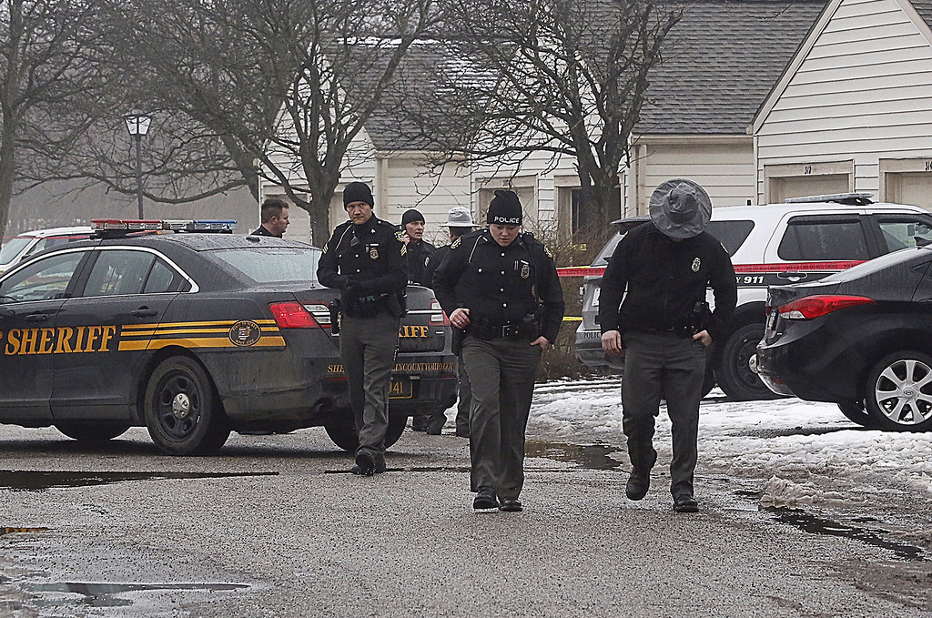 . Police investigate the scene of a shooting in Westerville, Ohio, on Saturday, Feb. 10, 2018.  Westerville police have confirmed that two officers have been fatally shot at a home in the Columbus suburb.  A police statement says the officers responded to a 911 hang-up call around 11:30 a.m. and were shot after they arrived at a residence.  A suspect is reportedly in custody.    (Tom Dodge/The Columbus Dispatch via AP)