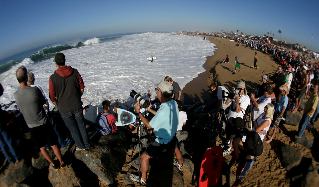 . A large crowd gathers to watch surfers and body surfer ride waves at the wedge on Wednesday, Aug. 27, 2014 in Newport Beach, Calif. Beach goers experienced much higher than normal surf, brought on by Hurricane Marie spinning off the coast of Mexico. (AP Photo/Chris Carlson)