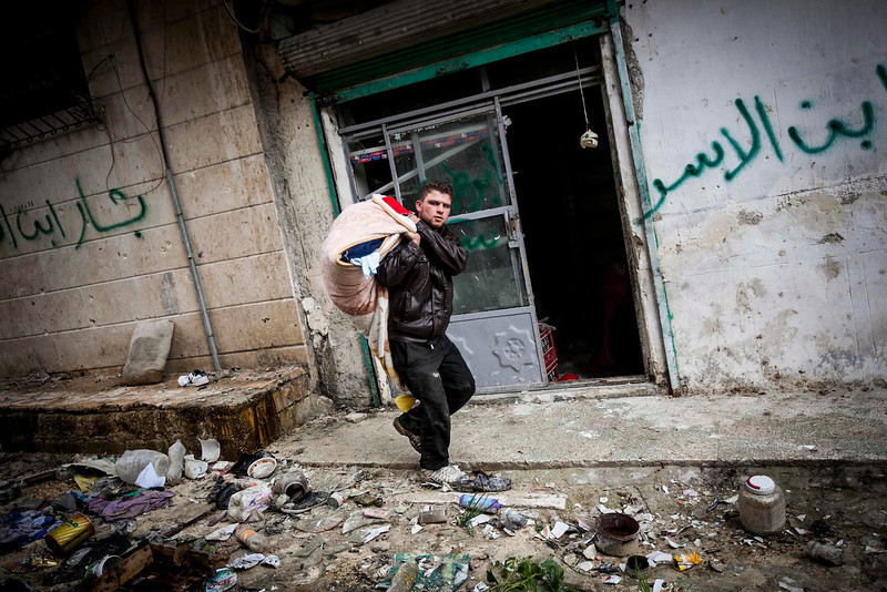 . In this Tuesday, Dec. 11, 2012 photo, a Syrian man carries his belongings after his home was damaged due to fighting between Free Syrian Army fighters and government forces in Aleppo, Syria. (AP Photo/Narciso Contreras)