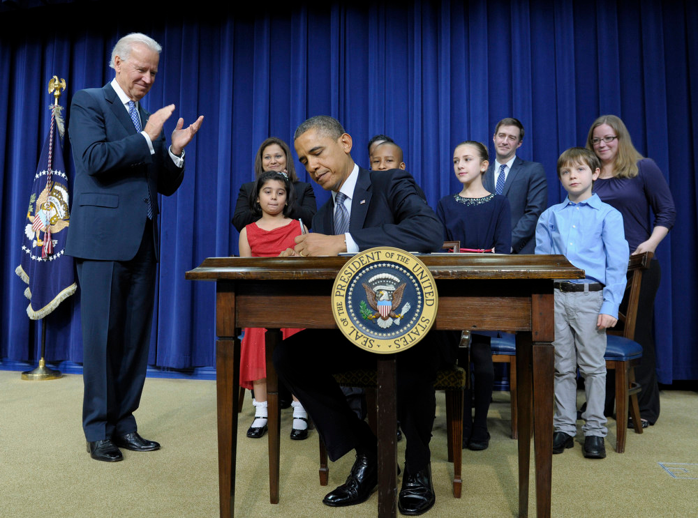 . President Barack Obama, accompanied by Vice President Joe Biden and children who wrote the president about gun violence following last month\'s shooting at an elementary school in Newtown, Conn., signs executive orders, Wednesday, Jan. 16, 2013, in the South Court Auditorium at the White House in Washington. The children and their parents from left, Hinna Zeejah, 8, and Nadia Zeejah, Hinna\'s mother, Taejah Goode, 10, and Kimberly Graves, Taejah�s mother, Julia Stokes, 11, and Dr. Theophil Stokes, Julia\'s father, and Grant Fritz, 8, and Elisabeth Carlin, Grant\'s mother. (AP Photo/Susan Walsh)