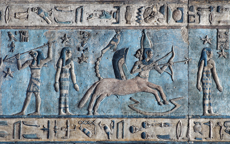 """[EGYPT 29587] 'Sagittarius on astronomical ceiling at Dendera.'  A winged centaur-like creature portrays the zodiac  sign Sagittarius on the astronomical ceiling in the outer hypostyle hall of the Hathor Temple at Dendera. The ceiling consists of seven separate strips but here we are looking at a detail of the upper register of the WESTERNMOST STRIP. Sagittarius is depicted with two heads, human in front, lion in back. He also has two tails, the upper one being a scorpion's tail, turned back. There are six zodiac signs depicted in the entire westernmost strip (see picture 29585 till 29590) and the other six can be found on the easternmost ceiling strip of the hall (see picture 29526). These signs are of Babylonic-Greek origin and are not found in Egypt before it was conquered by Alexander the Great in 332 BC. The falcon above Sagittarius is a personification of the planet Jupiter. Standing on either side of Sagittarius, the two goddesses who have a star above their head are personifications of the third and fourth hour of the night. On the left a falcon-headed god who is named """"Horus, fighter against enemies"""" is spearing Seth (who is outside the frame of the picture, but see photo 29586). This Horus likely represents one of the circumpolar constellations. This part of the Dendera Temple was built during the Roman period (first century AD). Photo Mick Palarczyk."""