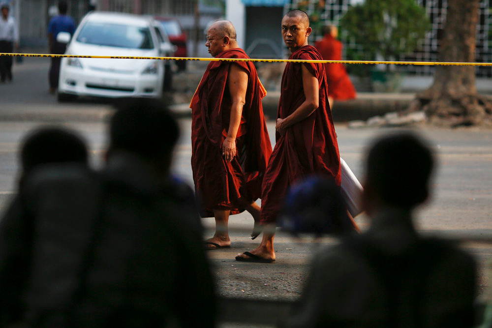 . Buddhist monks walk past a police line and security personnel near an Islamic school where 13 boys were killed after a fire on Tuesday, in the central, multi-ethnic Botataung district of the former capital Yangon April 3, 2013. Security has been tightened in parts of Myanmar\'s biggest city and former capital Yangon after the incident. REUTERS/Damir Sagolj