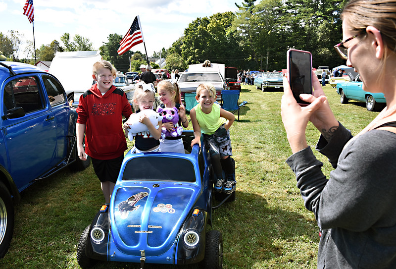 Mom Kelly Merrill of Townsend on right takes a snapshot of her kids in a MiniMe VW, kids L-R, Kaden Cotty 11, twin sisters Adasyn and Kahli Cotty 5, and Andyn Cotty 8, the car is owned by Duwayne Erickson of Raymond NH., he took a toy car and modified it with a go-kart engine and a BBQ grill under the front hood and working lights. SUN/David H. Brow