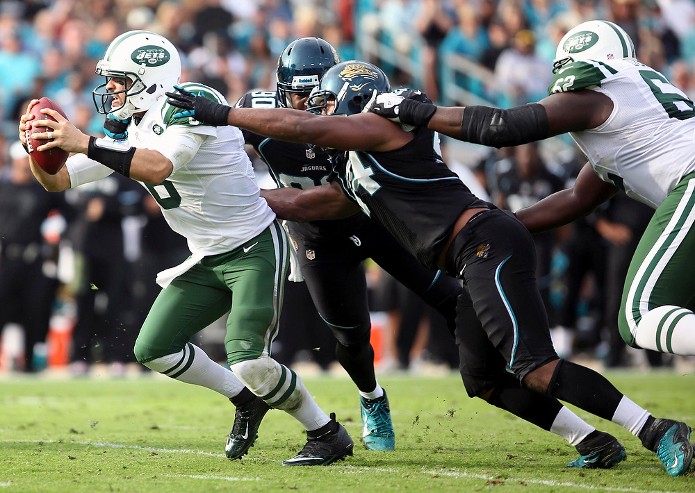 . New York Jets quarterback Mark Sanchez (L) is tackled by Jacksonville Jaguars defensive lineman Jeremy Mincey (C) during the second half of their NFL football game in Jacksonville, Florida December 9, 2012. REUTERS/Daron Dean (UNITED STATES - Tags: SPORT FOOTBALL)
