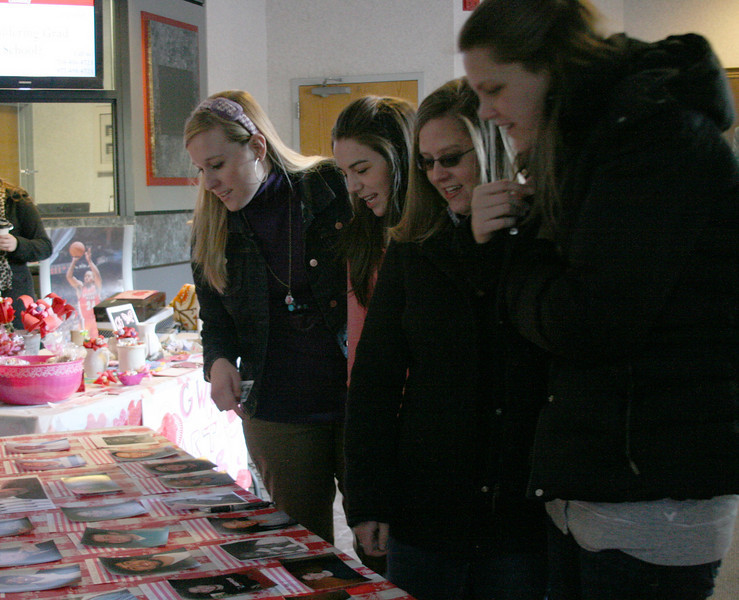Several students decide which candidates they will bid on for the Valentine Auction.