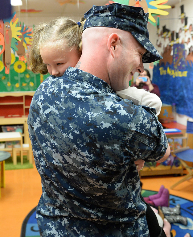. Navy Chief Nick Elliot hugs his daughter Alexis, 4, after surprising her inside her classroom at First Lutheran Children\'s Center in Redlands,CA. Thursday, Nov. 21, 2013. Elliots was deployed overseas for eight months, serving in the Persian Golf on the USS Harry S. Truman, this has been the longest he has ever been away from his family. (John Valenzuela/Staff Photographer)